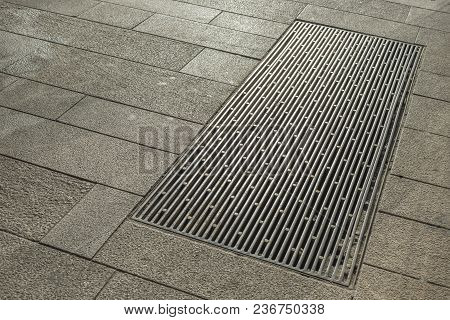 Big Metallic Hatch On Tiled City Pavement