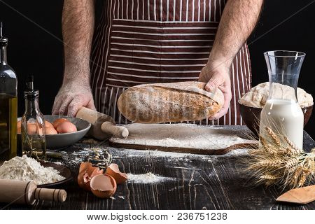 Chef Holds The Fresh Bread In Hand. Man Preparing Dough At Table In Kitchen. On Black Background. He