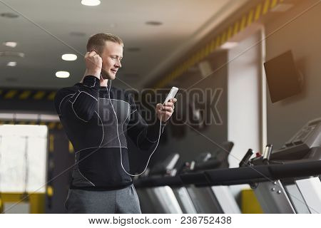 Young Man With Smartphone Before Running On Treadmill In Gym. Fitness Guy Jogging In Fitness Club, L