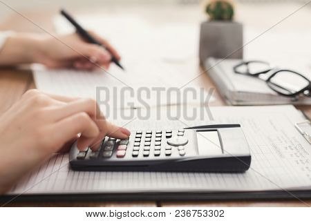 Closeup Of Woman Hand Counting Account On Calculator And Writing In Documents. Financial Background,