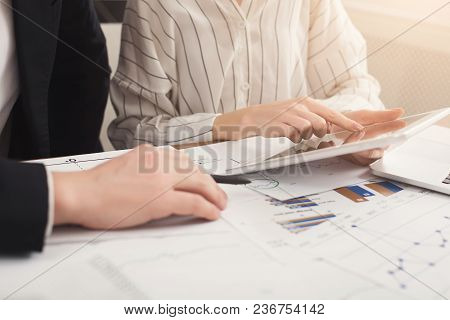 Closeup Of Business Colleagues Hands Using Tablet And Working With Documents. Financial Background,