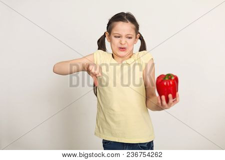 Little Girl Standing With Bell Pepper And Showing Thumb Down Over White Background. Healthy Food For
