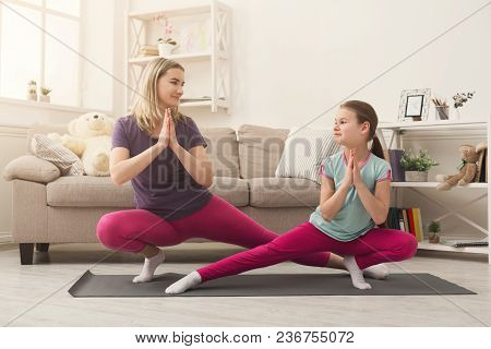 Young Woman And Child Daughter Doing Yoga Exercise And Stretching At Home. Health, Sport, Leasure Co
