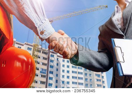 Builder Shaking Hands With Businessman In The Background Of A Construction Crane.