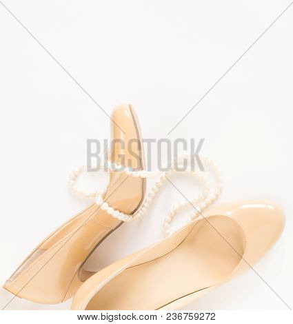 Cream Heeled Women's Shoes And Pearls Necklace On White Background.