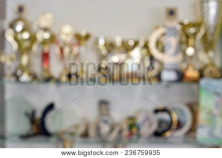 Blurred Background Of Golden Sportive Trophy Cups On Shelf