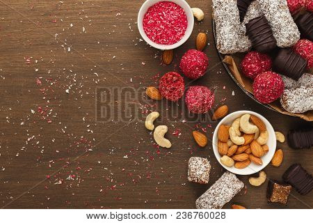 Top View On Wooden Table With Variety Of Healthy Raw Vegan Candies, Almonds, Hazelnuts, Dates. Fitne