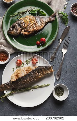 Restaurant Food - Whole Grilled Dorado And Sea Bass On Black Restaurant Table With Cutlery, Mediterr