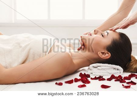 Woman Enjoying Anti Aging Facial Massage, Lying On Table With Rose Petals. Pretty Girl Getting Profe