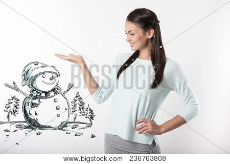 Lovely Snowman. Kind Cheerful Young Mother Showing A Pretty Little Snowman And Smiling