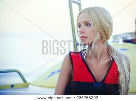 A Tender Beautiful Blond Woman On A Cutter Is Wearing A Life Jacket. Gentle And Bright On A Sea Crui
