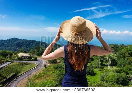 Young Traveling Woman In Hat And Standing On The Top Of The Mountain Cliff Before Beautiful View Of
