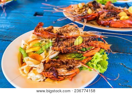 Tasty Lobsters And Jumbo Prawns Prepared With Garlic And Lime On Tropical Background. Traditional La