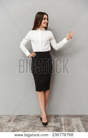 Full length portrait of brunette businesswoman 20s in white shirt and black skirt looking aside and pointing finger aside on copyspace isolated over gray background