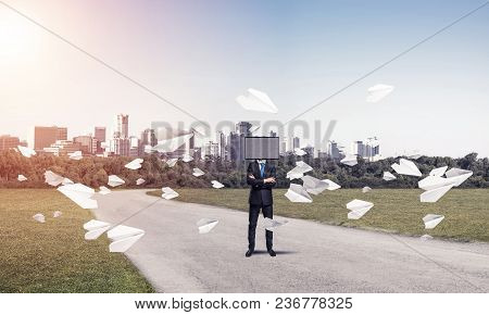 Businessman In Suit With Tv Instead Of Head Keeping Arms Crossed While Standing On The Road Among Fl