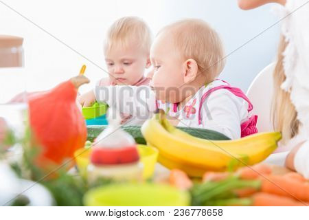 Portrait of a cute baby girl with blue eyes eating healthy solid food, while sitting in a high chair next to another baby in a modern daycare center for babies