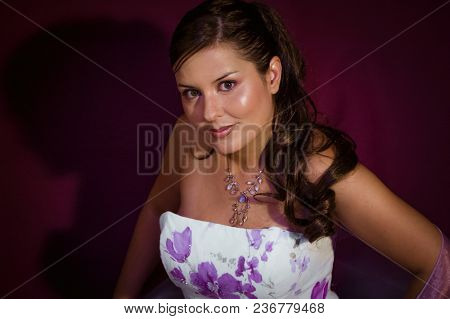 beautiful woman dressed as bridesmaid in white dress with violet flowers