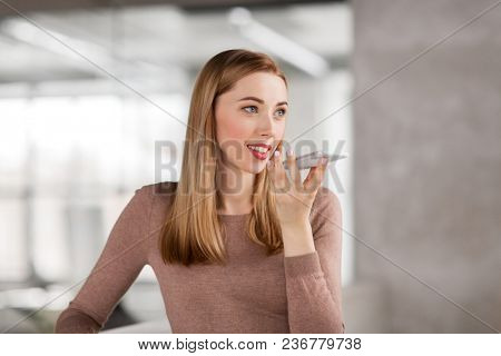 business people, technology and corporate concept - happy smiling businesswoman using voice command recorder on smartphone at office