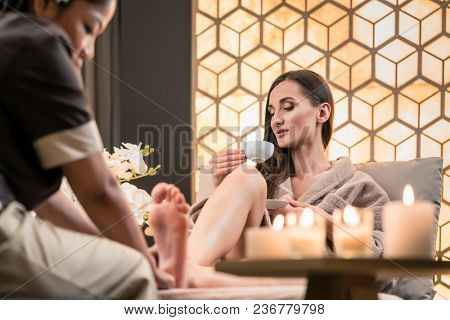 Professional wellness therapist massaging the foot of a female client in Asian beauty center