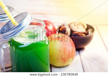 Smoothie in glass jar on rustik wood. Green healthy beverage and fresh fruit.