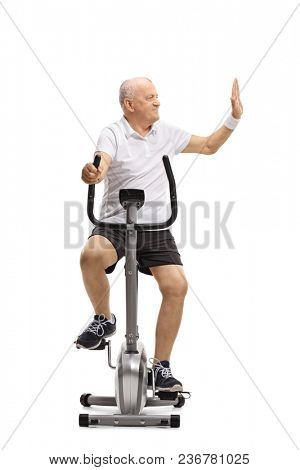 Mature man riding a stationary bike and making a high-five gesture isolated on white background