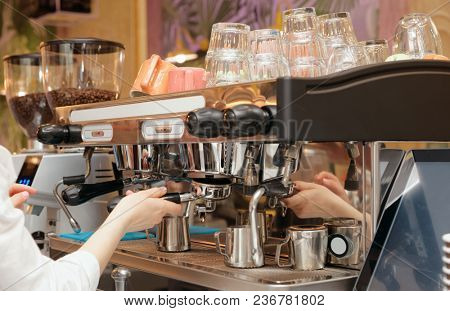 Barista is brewing coffee in a restaurant with professional espresso maker