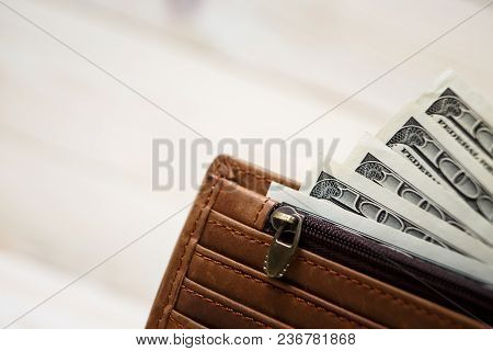 Dollar Bills And Leather Wallet On Wooden Background