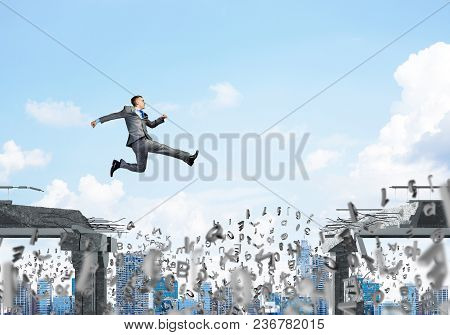 Businessman Jumping Over Gap With Flying Letters In Concrete Bridge As Symbol Of Overcoming Challeng