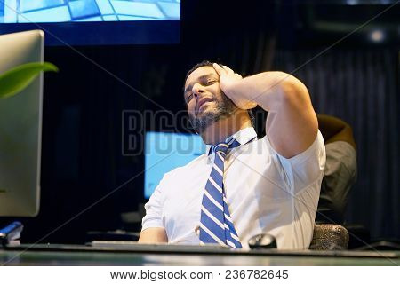 Businessman Suffering From Headache Sitting In Front Of Computer. Close-up Of Office Worker With A H