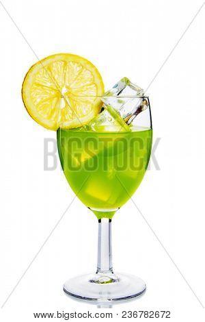 Glass of green apple juice with slice of orange