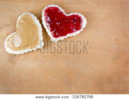 Peanut Butter And Jelly Sandwitch Cut In A Heart Shape On A Wooden Board