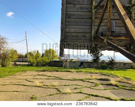 Outdoors Basketball Court During Sunny Day. Basketball Court Overgrown With Grass. School Yeard, Sun