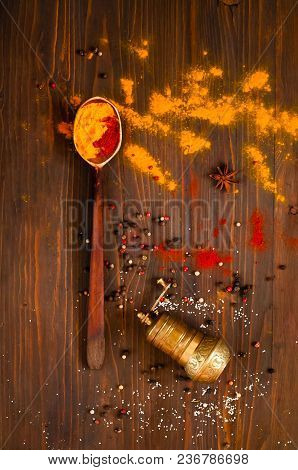 Wooden Spoon, Pepper Mill   And Ingredients On A Dark Background. Background With Spices, Turmeric,
