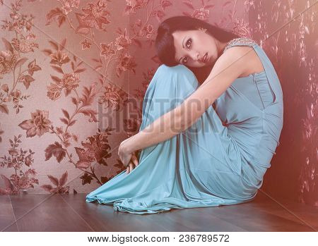 Woman  in evening dress against the decorated wall background