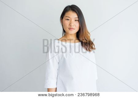 Serious Beautiful Young Chinese Woman In White Blouse Looking At Camera. Portrait Of Calm Confident