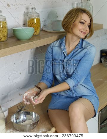 Young Attractive Girl Is Preparing Cookies In The Kitchen. She Molds Molds From Dough.