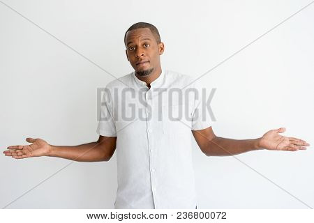Puzzled African Man With Beard Shrugging Shoulders And Looking At Camera. Confused Frowning Handsome