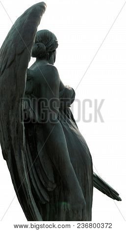 An Angel Statue Isolated, Facing The Sun, With Large Curving Wings.