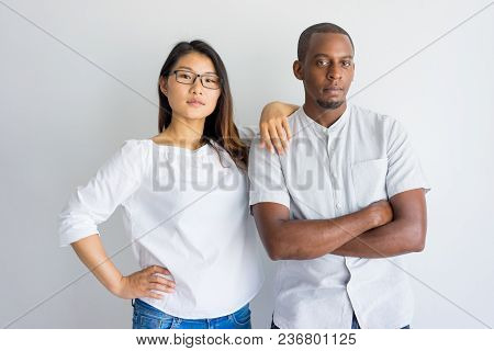 Serious Confident Young Multiethnic Couple Looking At Camera And Standing In Studio. Modern Asian Wo