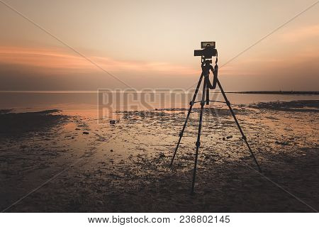 Dslr Digital Professional Camera Stand On Tripod Photographing Sea, Twilight Sky And Cloud Landscape
