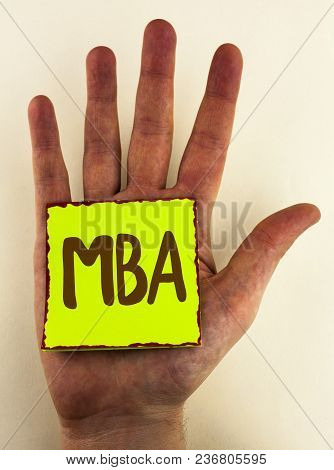 Handwriting text writing Mba. Concept meaning Master of Business Administration Advance Degree After College Studies written Sticky Note Paper placed Hand the plain background. poster