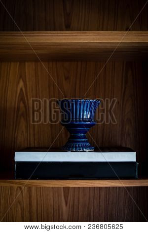 Blue Vase On Top Of Two Large Nondescript Book, All In Dark Shelf, Natural Side Lighting.