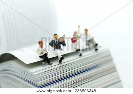 Miniature People: Business Team Reading News Paper On Book. Image Use For Background Education ,busi