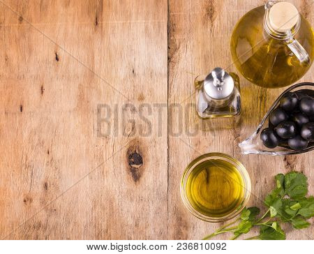 Olive Oil. Bottle Of Virgin Olive Oil. Olives And Healthy Olive Oil Bottles And Cup With Parsley On