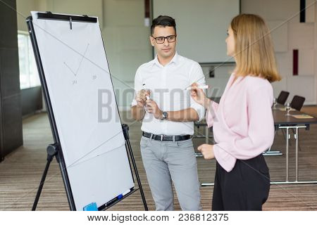 Confident Businessman And Businesswoman Discussing Strategy At Meeting. Young Caucasian Partners Or