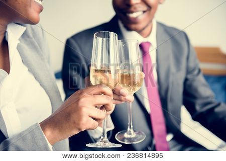 A couple celebrating with a bottle of champagne