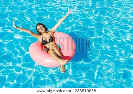 Young Happy Girl In Bikini Is Swimming In The Pool With A Pink Circle.