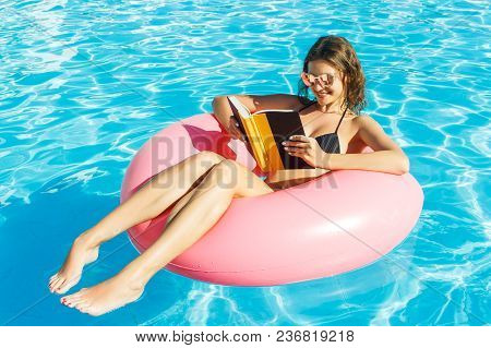 Young Happy Girl In Bikini Is Swimming In The Pool And Reading A Book With A Pink Circle.