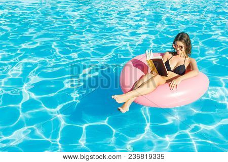 Beautiful Woman Reading A Book On Inflatable Ring In Blue Swimming Pool.