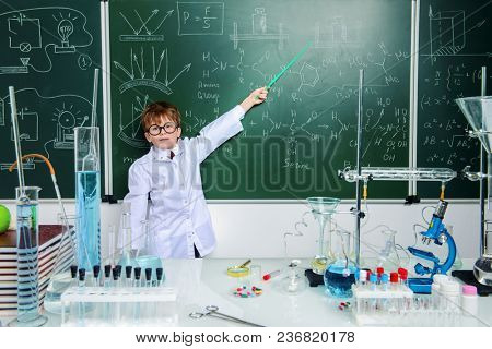 Clever schoolboy stands by a chalkboard on a chemistry lesson. Educational concept.